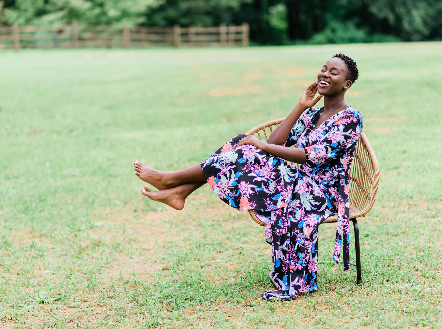 Black woman sits in chair, laughing in Fairmount Park in Philadelphia.