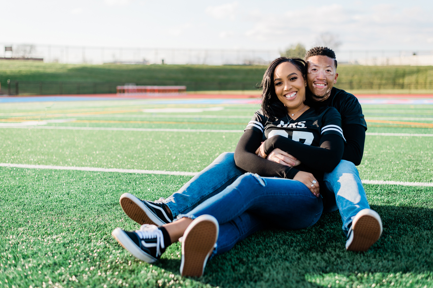 Black couple holding each other while seated in middle of football field. By Tonjanika Smith Photography