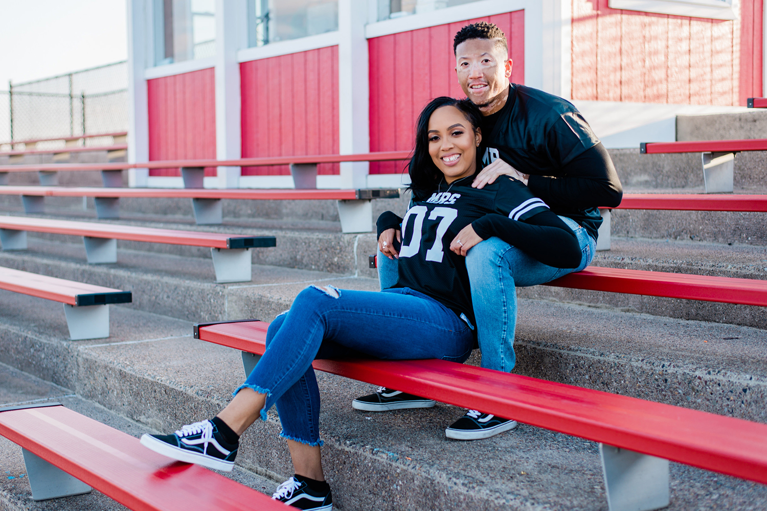 Black couple seated in bleachers with 07 and 26 on front of jerseys. By Tonjanika Smith Photography
