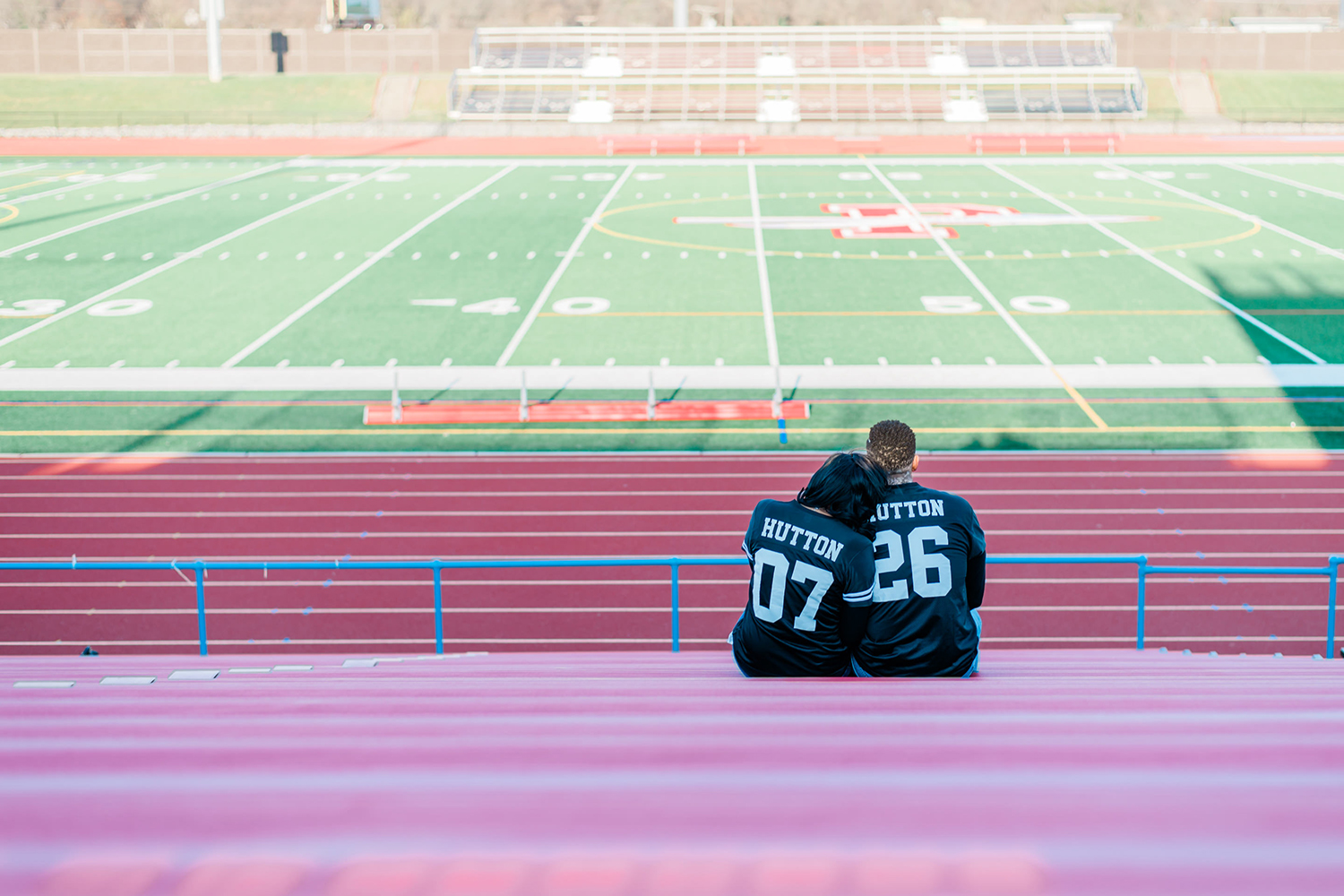 Black couple seated in bleachers with 07 and 26 on back of jerseys. By Tonjanika Smith Photography